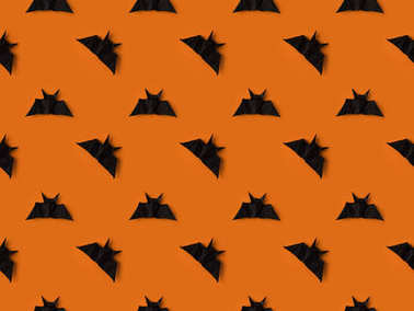 Halloween texture with black origami bats, isolated on orange stock vector