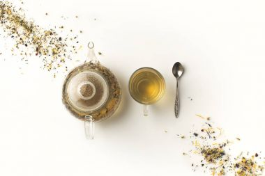 Herbal tea in cup and kettle