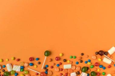 Top view of assorted colorful halloween treats on orange stock vector