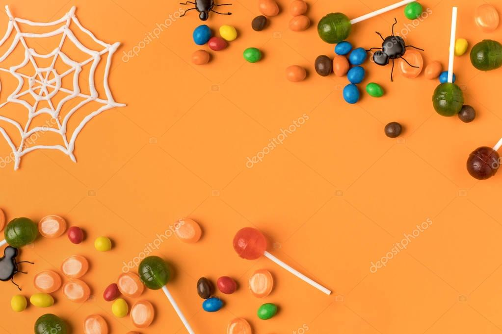 Top view of assorted colorful halloween treats with spiders and cobweb on orange