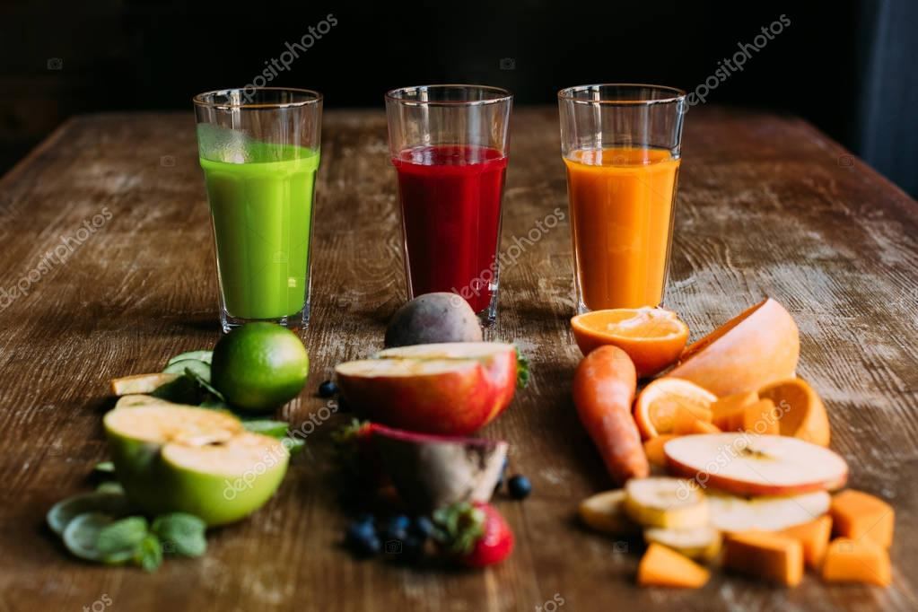 Close-up view of various organic fruit and vegetable smoothies with fresh ingredients on table stock vector