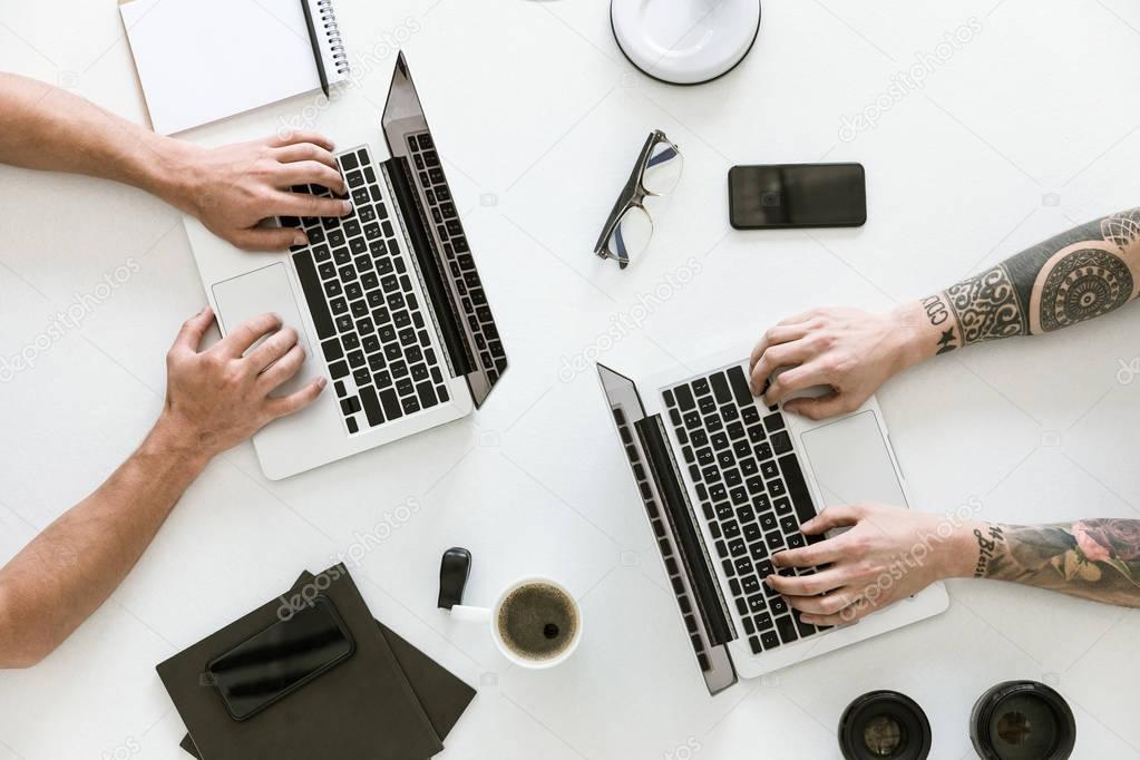 Two men working with laptops
