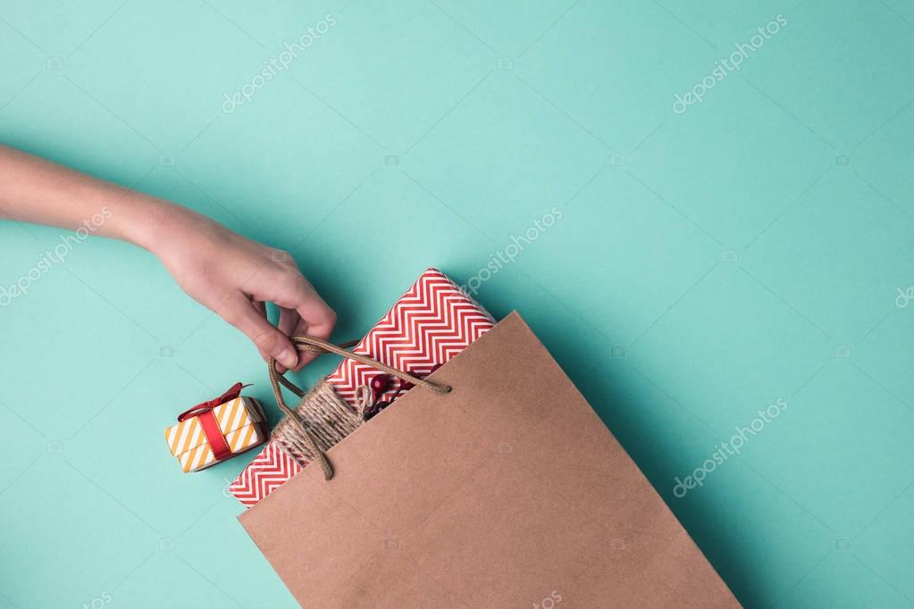 hand holding paper bag with gifts
