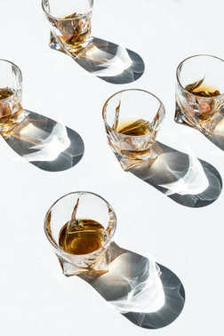 Close-up view of luxury whiskey in glasses with shadows on white stock vector