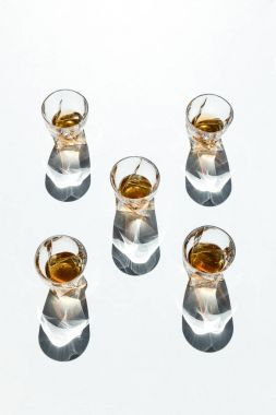 Five glasses with brown whiskey and shadows on white stock vector