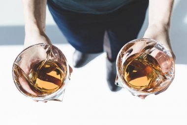 person holding glasses of whiskey