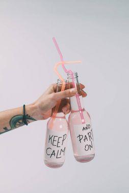 bottles of alcohol beverages in hand