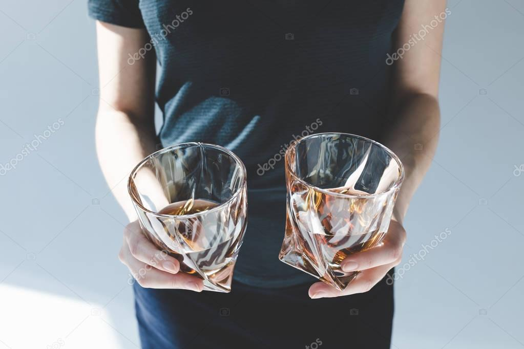 person holding glasses with brandy