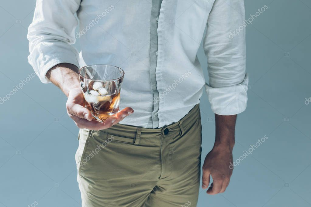 man holding whiskey with ice