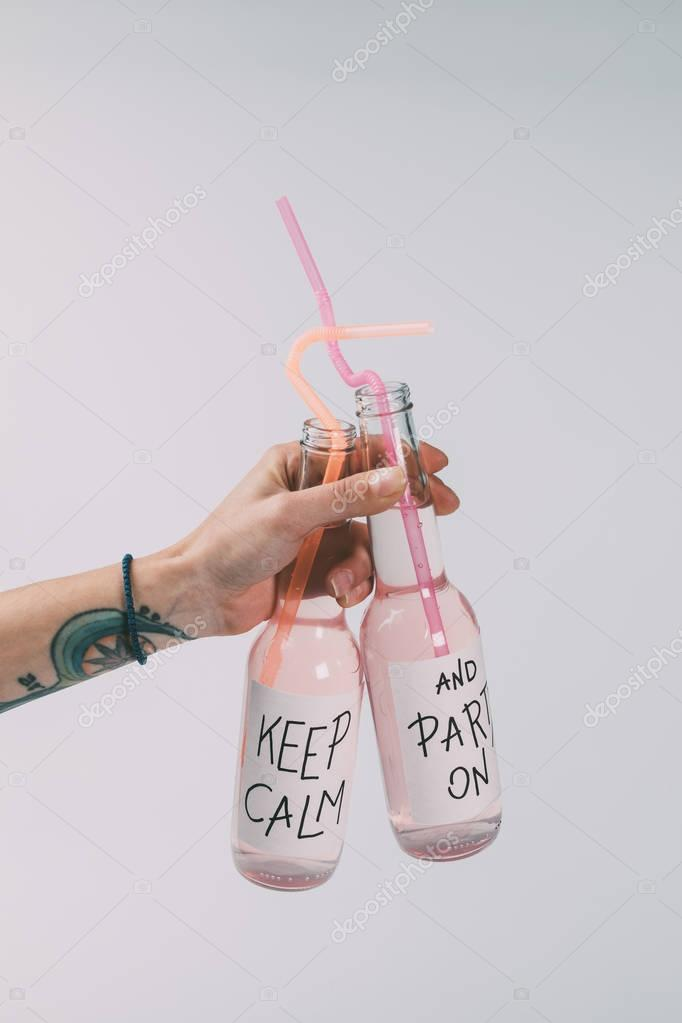 bottles of alcohol beverages in hand