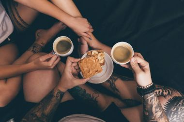 couple with toasts and coffee in bed