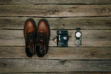 brown shoes with film camera and compass