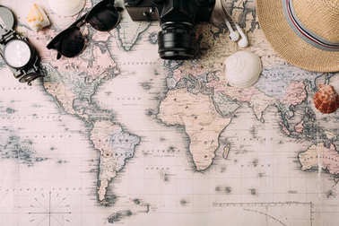 film camera with sunglasses and compass on map