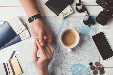 couple holding hands and planning travel