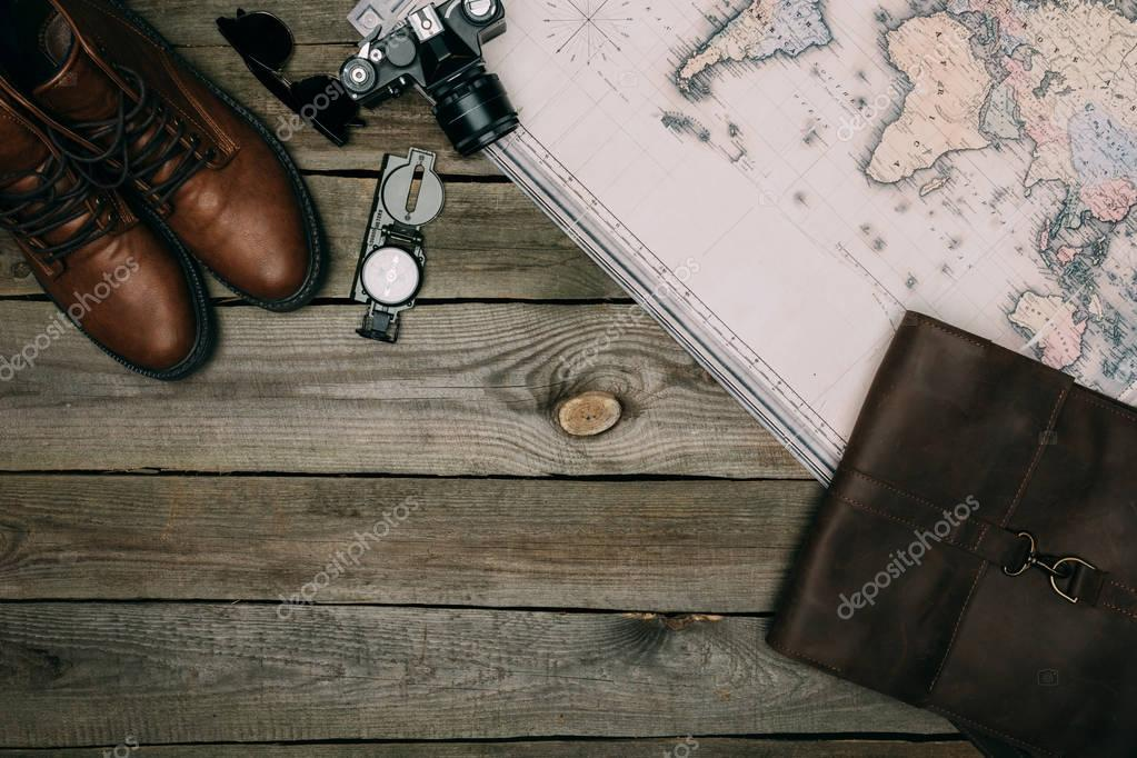 map with film camera and compass with shoes