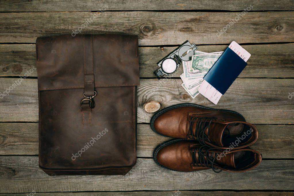 brown bag and shoes with passport and money