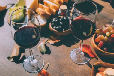 Close-up shot of glasses of red wine with various snacks and fruits on wooden table stock vector