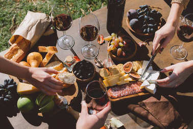 people drinking wine and eating outdoors
