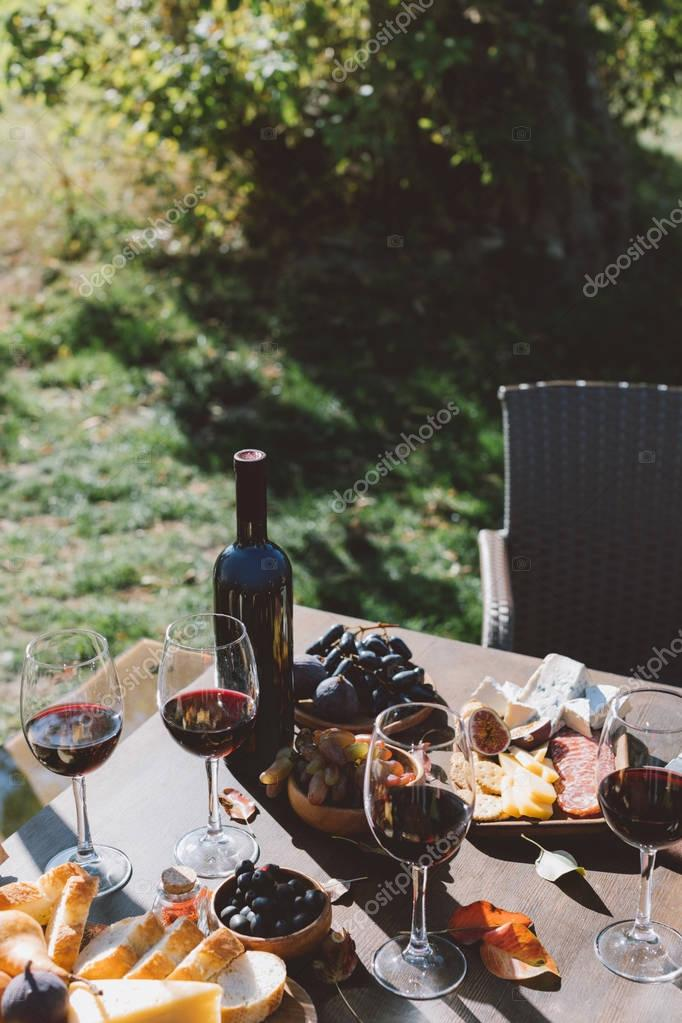 table with red wine and snacks