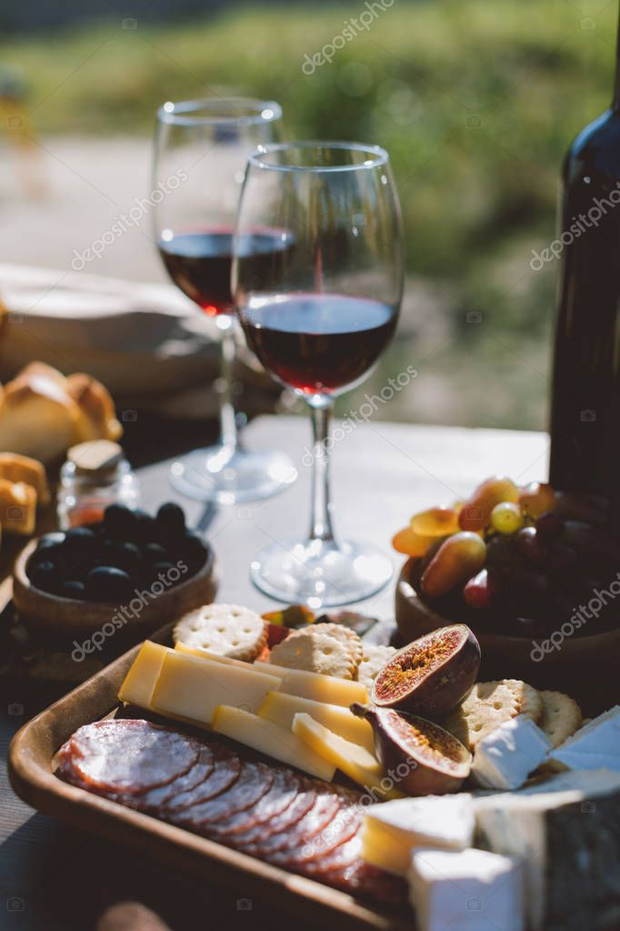 wine with wooden plate of sliced snacks