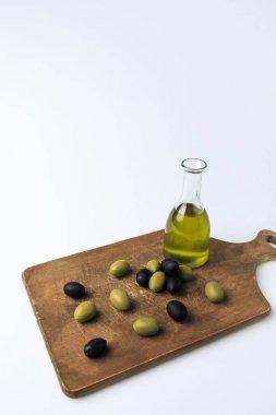 Bottle of olive oil and olives on board