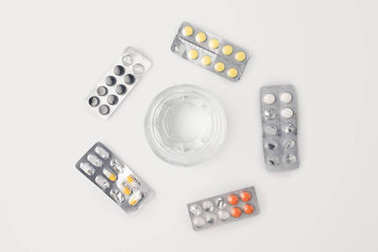 Top view of glass of water inside of circle of blister packs with different pills stock vector