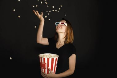 Woman in 3d glasses throwing up popcorn isolated on black stock vector