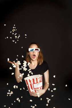 Shocked woman with bucket of popcorn isolated on black stock vector