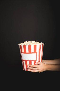 woman holding bucket of popcorn
