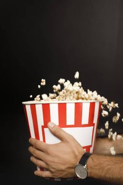 man holding bucket of popcorn