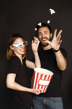 couple throwing popcorn at camera