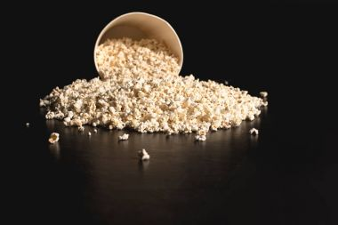 popcorn spilled from cardboard bucket