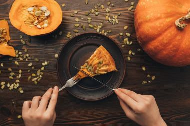 woman cutting pumkin pie