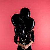 woman holding black balloons