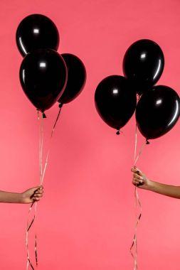 black balloons in hands