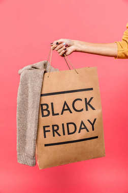 Cropped shot of person holding shopping bag with clothing and black friday inscription isolated on pink stock vector