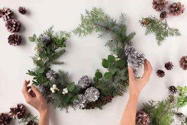 hands making christmas wreath
