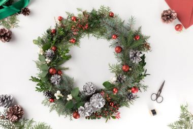 Top view of christmas wreath made of fir branches, christmas balls and pine cones with envelope, isolated on white stock vector