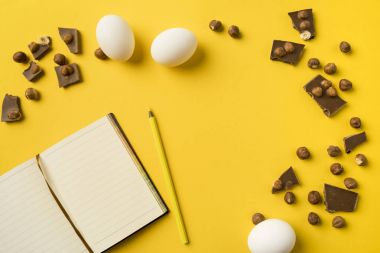 Notebook and pencil with chocolate and eggs