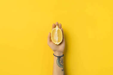 woman holding half of lemon