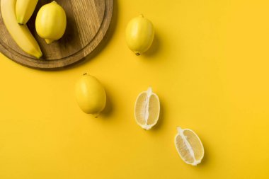 lemons and bananas with wooden board