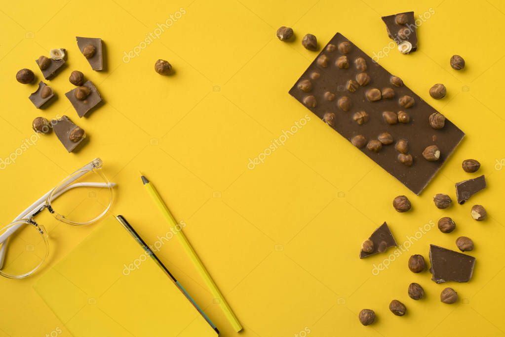 Notebook with pencil and chocolate