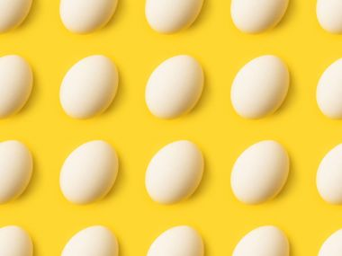 Set of unprocessed Chicken eggs isolated on yellow stock vector