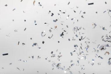 Falling silver confetti pieces