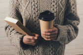 Fotografie woman in sweater with book and coffee