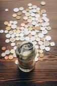Skleněná dóza s bankovky a mince