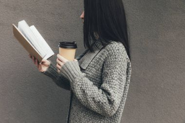 woman with book and coffee to go
