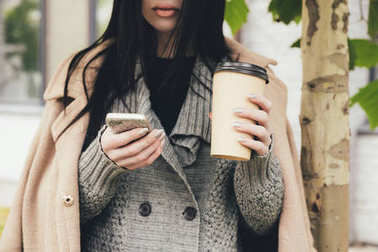 woman with smartphone and coffee