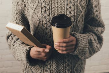 woman in sweater with book and coffee