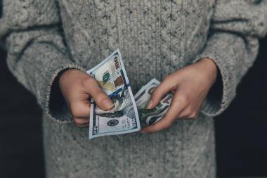 woman holding dollar banknotes